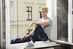 Germany, Berlin, Young man sitting at open window, smiling Stock Photos