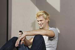 Germany, Berlin, Young man using smart phone, smiling Stock Photos