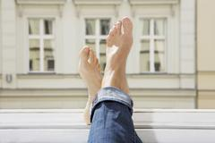 Germany, Berlin, Young woman feets on open window Stock Photos