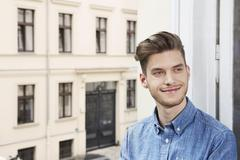Stock Photo of Germany, Berlin, Young man looking away, smiling