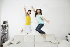 Germany, Berlin, Young women having fun and jumping on couch - stock photo