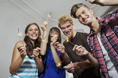 Stock Photo of Germany, Berlin, Group of young people waving sparklers