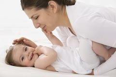 Mother cuddling daughter, smiling Stock Photos
