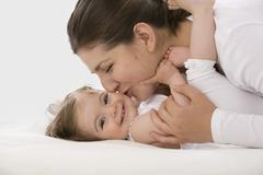 Stock Photo of Mother cuddling daughter, smiling