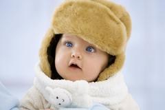 Stock Photo of Baby girl in fur hat with mouth open, close up