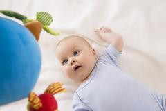 Stock Photo of Baby girl looking at toy, smiling