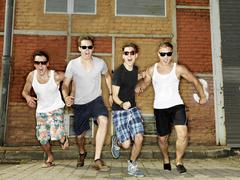 Stock Photo of Germany, Duesseldorf, Young friends running in industrial area