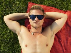 Stock Photo of Germany, Duesseldorf, Young man relaxing in meadow
