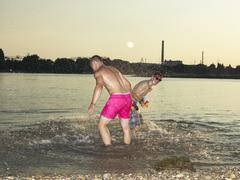 Germany, Duesseldorf, Young friends playing in water - stock photo