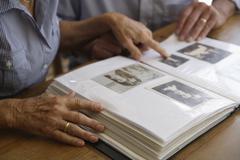 Germany, Bavaria, Senior couple with photo album - stock photo