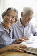 Germany, Bavaria, Senior couple with photo album, smiling - stock photo