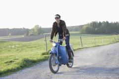Germany, Bavaria, Mature woman riding old moped of 1960s - stock photo