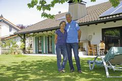 Stock Photo of Germany, Bavaria, Senior couple standing in yard, smiling