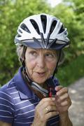 Germany, Bavaria, Senior woman with bicycle helmet, close up - stock photo