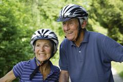 Germany, Bavaria, Senior couple with bicycle helmet, smiling - stock photo