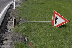 Germany, Bavaria, Bumps ahead sign lying on grass Stock Photos