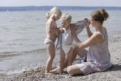 Germany, Bavaria, Mother and daughter helping son to undress Stock Photos