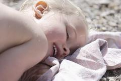 Germany, Bavaria, Girl lying on beach towel, smiling, close up - stock photo