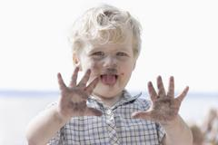 Germany, Bavaria, Boy playing with charcoal, smiling - stock photo