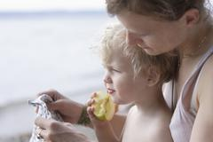 Germany, Bavaria, Mother with boy eating apple - stock photo
