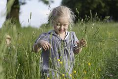 Germany, Bavaria, Girl walking through spring meadow - stock photo