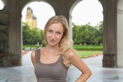 Stock Photo of Germany, Bavaria, Munich, Young woman standing in front of Theatine Church,
