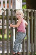 Stock Photo of Germany, Girl standing on fence in playground