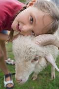 Germany, Munich, Girl with sheep in children's camp - stock photo