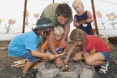Germany, Munich, Father with children preparing camp fire in tent - stock photo