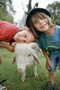 Germany, Munich, Boy and girl with sheep in children's camp - stock photo