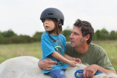 Germany, Munich, Father and son with horse in children's camp Stock Photos