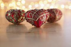 Heart shaped christmas tree ball on tomber floor, chain of lights in background - stock photo
