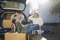 Couple relaxing on chair near car, smiling Stock Photos