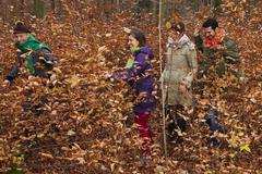 Germany, Berlin, Wandlitz, Men and women walking through bushes, smiling - stock photo