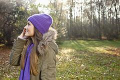 Stock Photo of Germany, Berlin, Wandlitz, Mid adult woman using cell phone, smiling