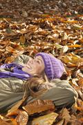 Stock Photo of Germany, Berlin, Wandlitz, Mid adult woman lying in foliage, smiling