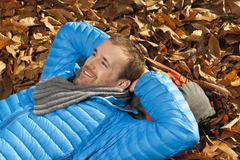 Stock Photo of Germany, Berlin, Wandlitz, Mid adult man lying in foliage, smiling