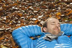 Stock Photo of Germany, Berlin, Wandlitz, Mid adult man lying in foliage