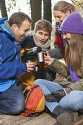 Stock Photo of Germany, Berlin, Wandlitz, Friends drinking hot beverage, smiling