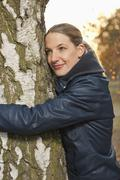 Stock Photo of Germany, Berlin, Wandlitz, Mid adult woman hugging tree, close up