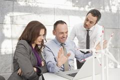 Germany, Leipzig, Business people using laptop and discussing about wind power - stock photo
