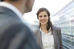 Stock Photo of Germany, Leipzig, Businesswoman smiling, businessman in foreground