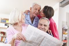 Senior men and women with newspaper,  woman kissing to man in background Stock Photos