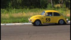 Bright yellow Volkswagen Beetle following Citroen 11B in racing, click for HD Stock Footage