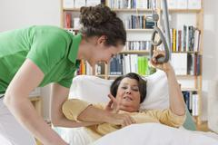 Stock Photo of Mid adult woman helping senior woman