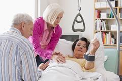 Vanhempi nainen makaa sängyssä, mies ja nainen istuu vieressä Kuvituskuvat