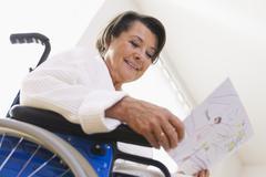 Vanhempi nainen istuu pyörätuolissa Kuvituskuvat