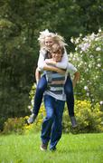 Stock Photo of Young man giving piggy back ride to woman