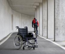 Austria, Mondsee, Young man on mountainbike with wheelchair in foreground - stock photo