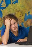 Teenage boy with laptop and map - stock photo